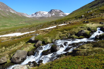 Peaceful landscape with a river flowing downhill and mountains in the background, Westfjords, Iceland