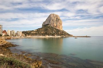Ifach mountain from shoreline with peaceful Mediterranean sea and blue sky with white clouds