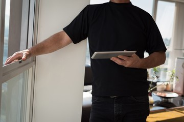 Man standing with digital tablet at home