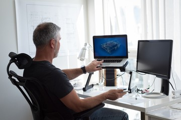 Man preparing architectural design on laptop and computer