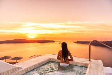 Luxury travel Santorini vacation woman swimming in hotel jacuzzi pool watching sunset. Europe resort destination holiday for honeymoon getaway.