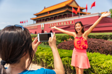 Wall Mural - China travel tourists taking picture with photo at Forbidden City in Beijing, China. Asia trip summer vacation. Two Asian women having fun taking photos at famous chinese landmark.
