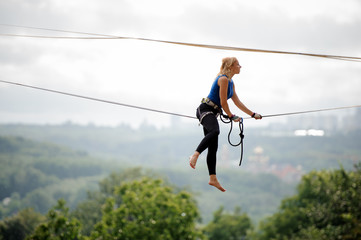 Side view young woman sitting on the slackline rope