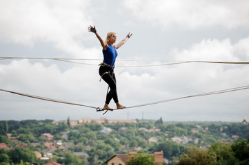 Young woman walking with arms raised on the slackline rope