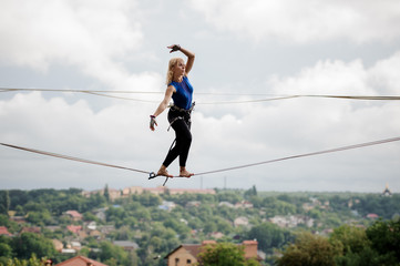 Young woman standing tilted her hands in the right direction on the slackline