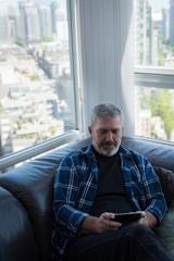 Man using digital tablet in living room