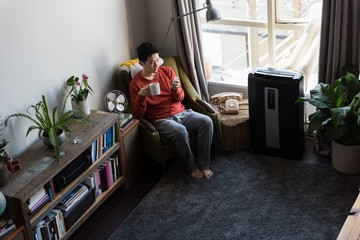 Man having coffee while using mobile phone in living room