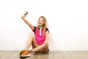 Beautiful teenage girl sitting on wooden floor taking selfie shots on her cell phone. Casual young female in yellow sneakers photographs herself on smartphone, leaning on wall. Background, copy space.