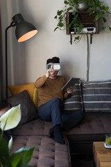 Man in virtual reality headset using digital tablet in living