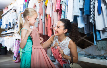Young interested woman with small girl in kids apparel boutique