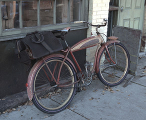 Old red bicycle with black bag