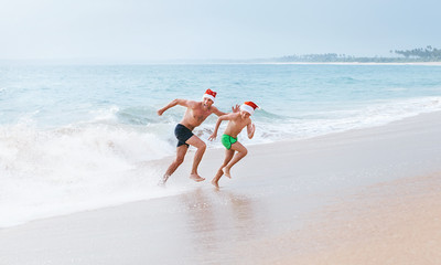 Father and son have a fun on ocean beach, run away from big waves. Christmas holiday time. Tropical vacation