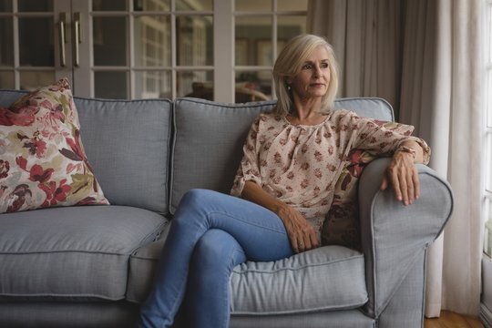 Thoughtful senior woman sitting on sofa at home
