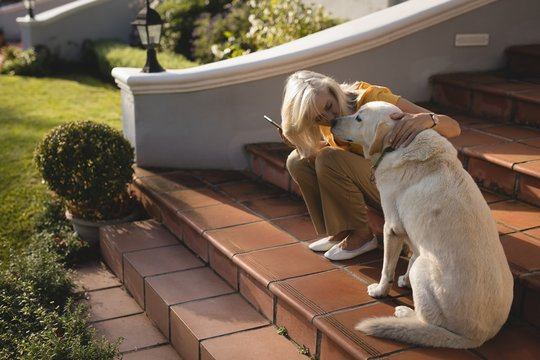 Senior woman kissing dog on the entrance steps