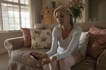 Senior woman with glucose meter checking blood sugar level at