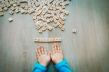 little girl play with letter puzzle in school or daycare