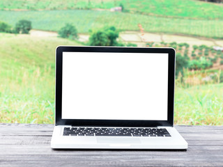 Laptop with blank screen on wooden desk and nature background