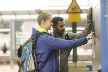Couple at a train station buying a ticket from a ticket machine