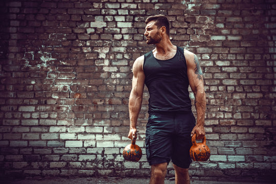 Athletic man working out with a kettlebell in front of brick wall. Strength and motivation. Outdoor workout.