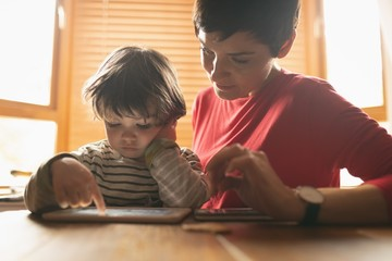 Mother teaching to son on digital tablet at home
