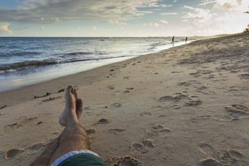 Legs of a Brazilian man enjoying vacation holidays at a tropical beach lansdcape in Praia do forte, Bahia, Brazil.