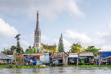 Aluminium Prints Asian Famous Place One of the banks of the Mekong river with the Cathedral of Cai Be, a river-land mixed town in Vietnam