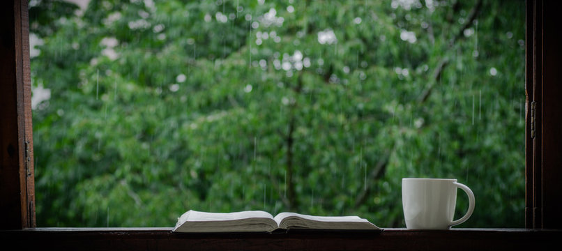 Cozy summer still life: cup of hot coffee and opened book on vintage windowsill and rain outside. Apartment. Rain in the summer