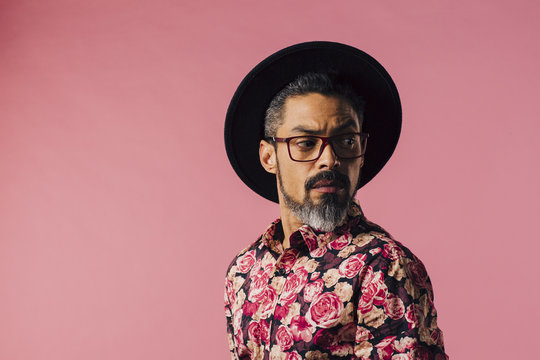 Portrait of a very cool man with tilted hat looking to side, isolated on pink studio background