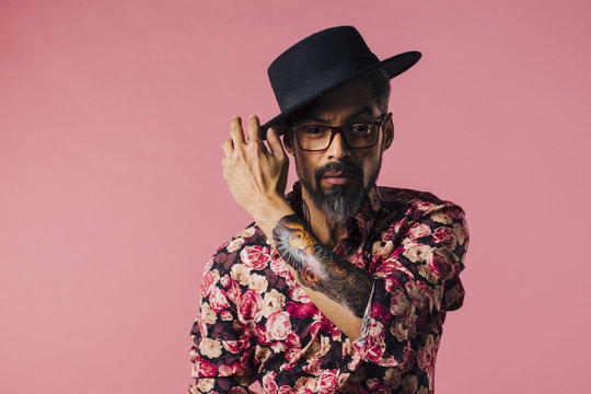 Portrait of a very cool mature artist with tattoo and glasses, touching his hat, isolated on pink studio background