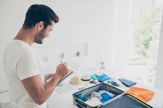 It's better to make a list! Joyful brunet man in a white T-shirt writes down what to take with him on a trip