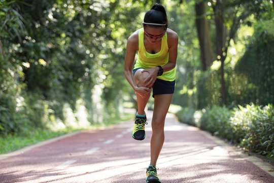 Female runner suffering with pain on sports running knee injury .