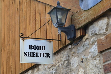 Bomb shelter sign on the wall in village of Beer in East Devon