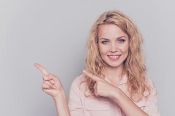 Attractive cute curly-haired blonde gorgeous caucasian charming young smiling girl wearing formal wear shirt pointing fingers. Copy space. Isolated over grey background