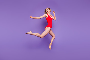Full-size portrait of attractive young woman model with blond hair flying looking back and laughing isolated on violet background