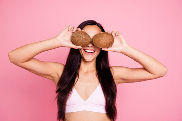 Big staring pop eyes concept. Close up studio photo portrait of pretty cute with long straight brunette brown hair lady with beaming toothy smile holding coconuts isolated on pastel bright background