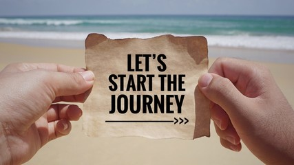 Motivational and inspirational quote - Hands holding a white piece of paper with text 'Let's start the journey' on it. Vintage styled background.