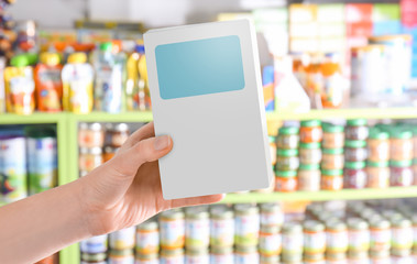 Woman holding package with baby milk formula in store
