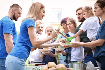 Volunteers serving food for poor people outdoors