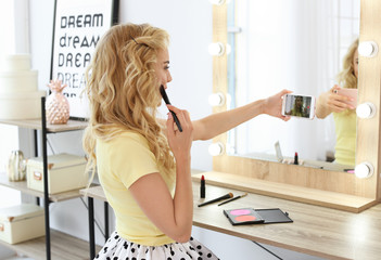 Beauty blogger filming makeup tutorial with smartphone in front of mirror at dressing table indoors
