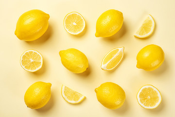Flat lay composition with whole and sliced lemons on color background