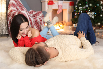 Happy young couple lying on floor at home. Christmas celebration