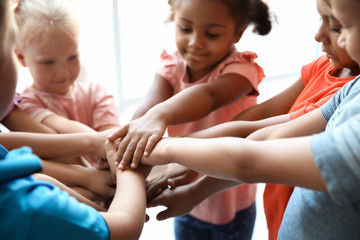 Little children putting their hands together, closeup. Unity concept