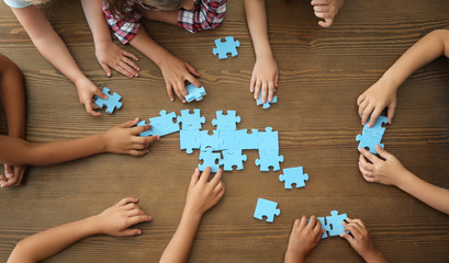 Top view of little children playing puzzle together at table, focus on hands. Unity concept