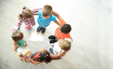 Little children making circle with hands around each other indoors, top view. Unity concept