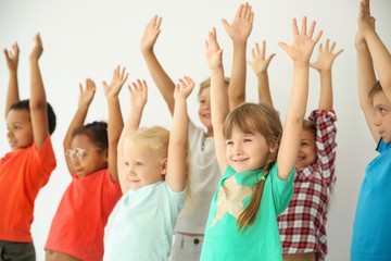 Little children raising hands together on light background. Unity concept