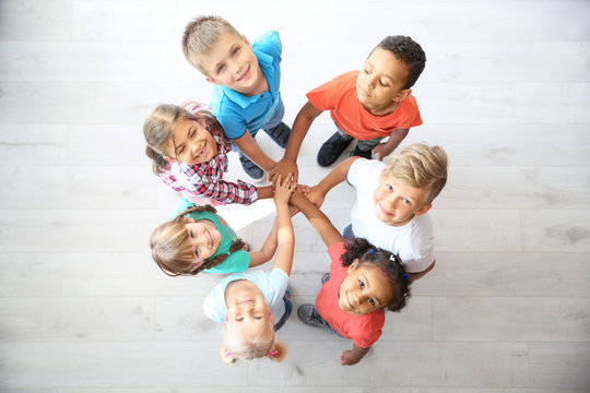 Little children putting their hands together indoors, top view. Unity concept