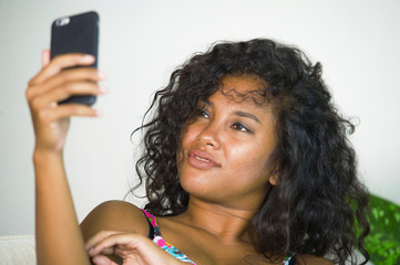 young attractive and beautiful happy black African American woman taking selfie portrait picture with mobile phone at holidays apartment