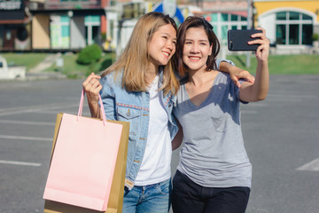 Attractive beautiful asian woman using a smartphone while shopping in the city. Happy young asian teenage at urban city while taking self portraits with her friends together with a smartphone.