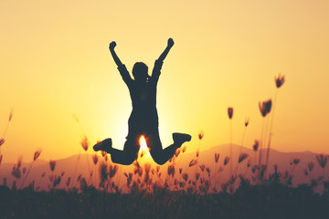 Freedom and adventure - woman happy at meadow . Free cheering girl with arms raised enjoying serene sunset in winning pose with arms stretched.