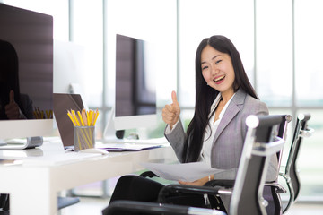 Beautiful Asian business woman sitting and smiling on chair in modern office with new desktop computers.